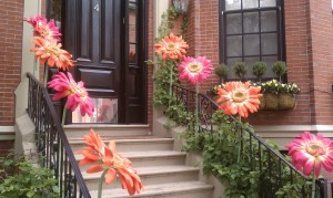 Eight oversized, fake orange and pink flowers line the railing leading to a lovely black Back Bay door