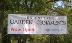 New England Garden Ornaments Sign strung between trees