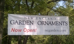New England Garden Ornaments Sign strung between trees
