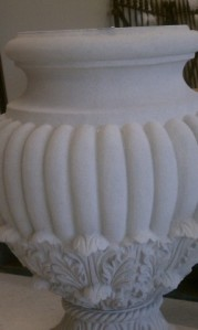 White fluted urn iwth flourishes at the base