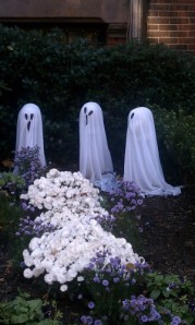 Three small white ghosts behind purple and white mums
