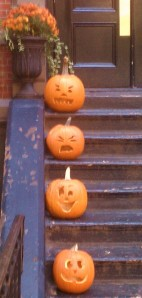 Four carved pumpkins on black outdoor stoop stairs